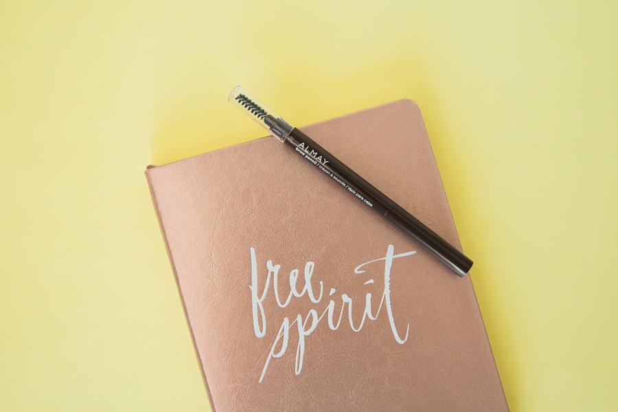 """lápiz para recrear ceja de ALMAY sobre una libreta rosa metálica con la leyenda """"free spirit"""". Todo eso sobre un fondo amarillo."""