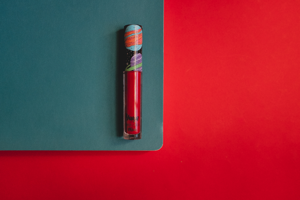 labial líquido mate de Yuya en el tono mi amor sobre libreta verde turquesa que a su vez está sobre un fondo rojo.