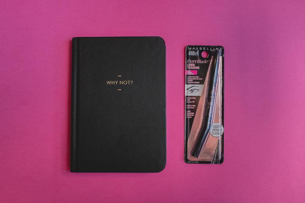 Delineador Curvitude de Maybelline en su empaque sobre fondo rosa a un lado de una libreta