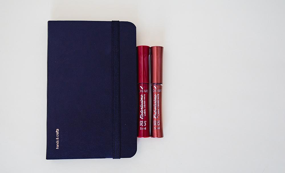 Dos labiales líquidos Colorissimo de Vogue sobre fondo gris a un lado de una libreta