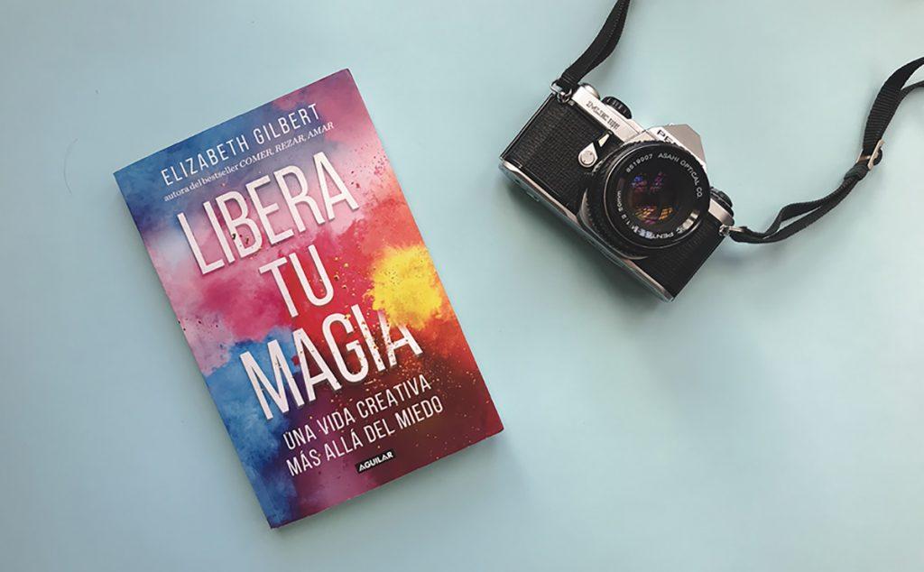 Portada del libro de autoayuda Libera tu magia de la autora Elizabeth Gilbert en un fondo azul pastel al lado de una cámara pentax análoga