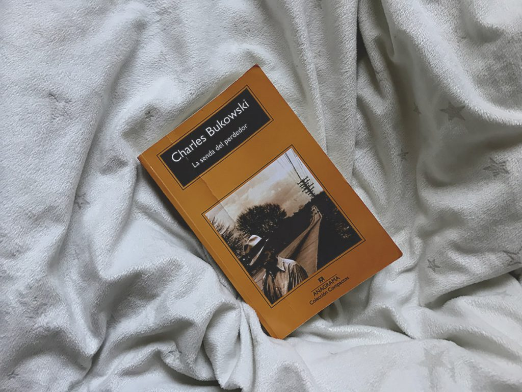 Libro La senda del perdedor de escritor Charles Bukowski sobre una cobija blanca.