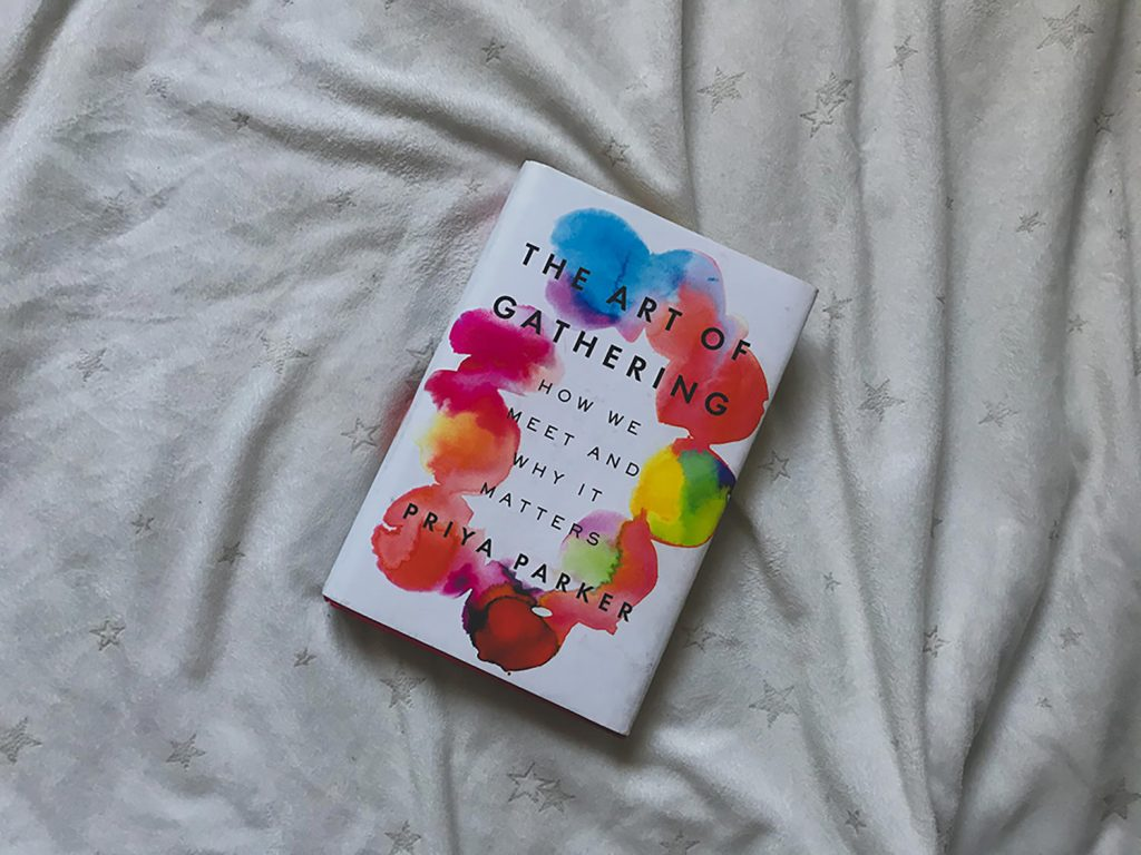 Portada del libro The art of gathering de la autora Priya Parker, sobre una colcha blanca