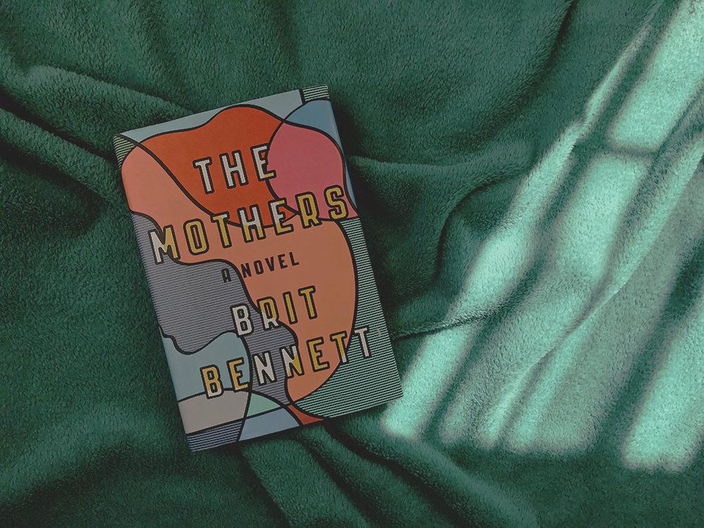 Libro novela The Mothers de la escritora Brit Bennett sobre cobija verde. La portada es muy colorida, es el perfil de la cara de una mujer pero muy abstracto, sin ojos ni detalles, solo líneas en la piel y bloque de colores naranja y rojo en el cabello.